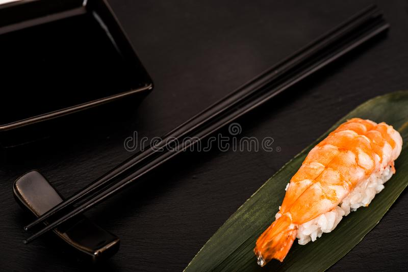 Close up of nigiri sushi with shrimp served with chopsticks and soy sauce royalty free stock photo