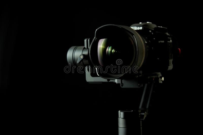 Close-up of a Nikon D750 DSRL camera using a Zhiyun Crane-2 stabilizer, with low-key lighting and a black background. Grenoble, France - May 23, 2019: Close-up stock image