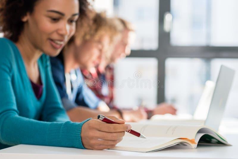 Close-up no estudante que guarda uma pena sobre um livro ao estudar foto de stock royalty free