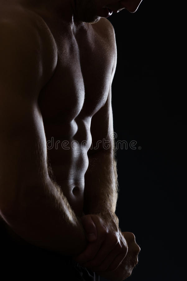 Close up no homem que mostra o corpo muscular no preto imagem de stock royalty free