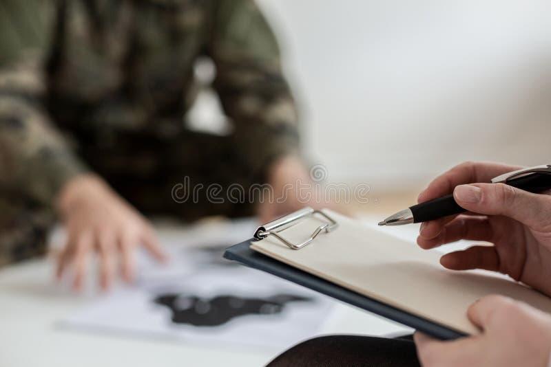 Close-up no psychotherapist que toma notas ao analisar o comportamento do soldado durante a reunião imagens de stock