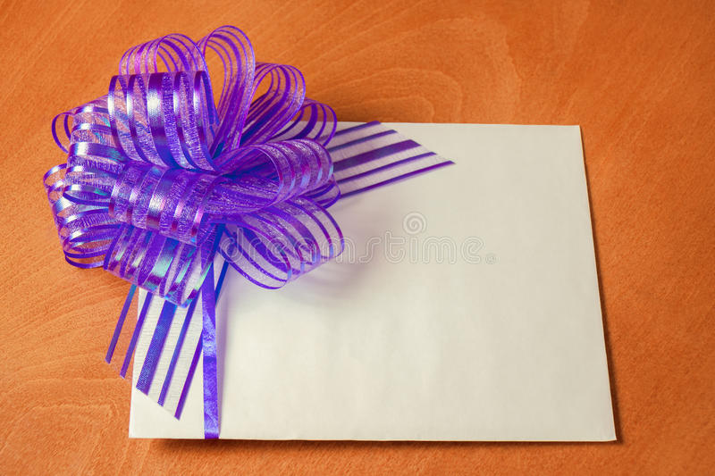 Close up of a note card with violet bow. On wooden background royalty free stock images