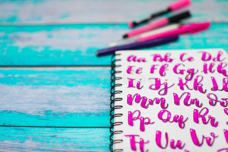 Close up of notebook with hand drawn abc alphabet letters and colorful pens on blue wooden desk background. Back to school concept royalty free stock photo