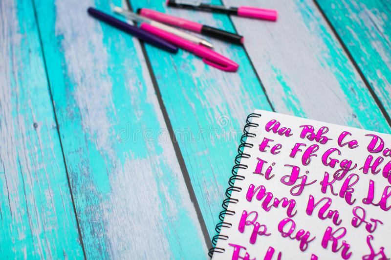Close up of notebook with hand drawn abc alphabet letters and colorful pens on blue wooden desk background. Back to school concept royalty free stock image