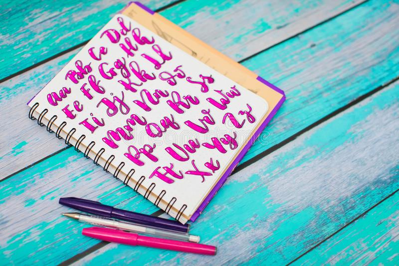 Close up of notebook with hand drawn abc alphabet letters and colorful pens on blue wooden desk background. Back to school concept royalty free stock images