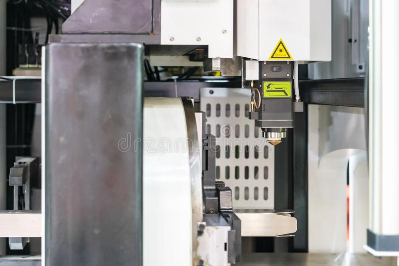Close up nozzle head and square pipe product prepare or setting by clamp with automatic feed and rotate unit of high precision cnc. Plasma laser cutting machine royalty free stock photography