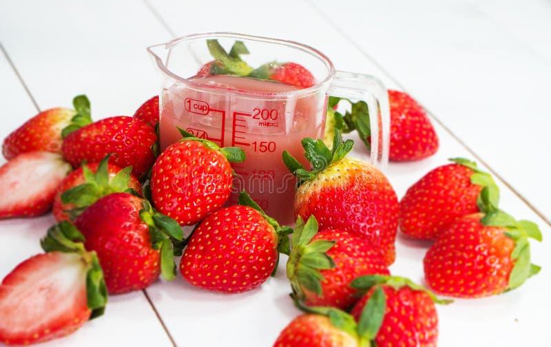 Close up o suco da morango e a morango vermelha em torno do frasco plástico, na placa da madeira imagem de stock