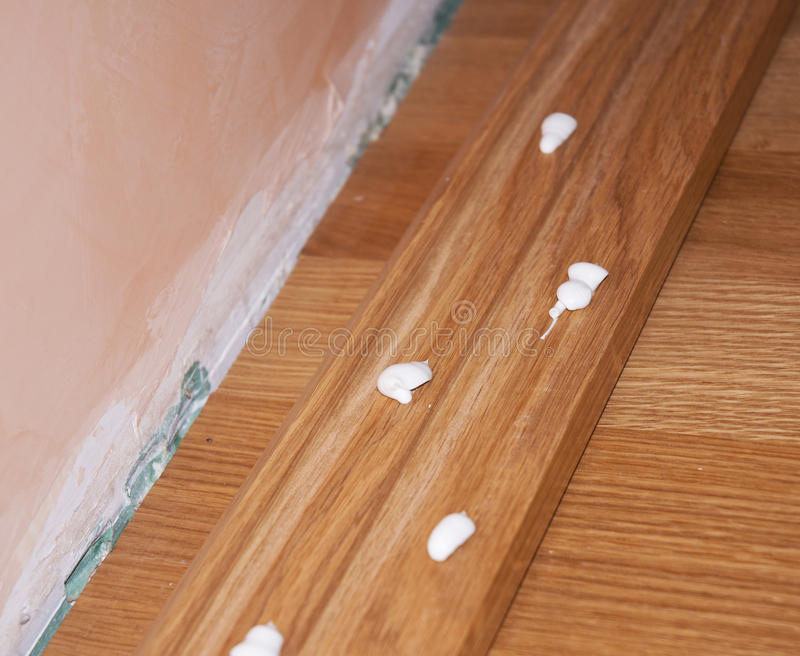 Close up on Oak Wood Parquet Installation. Caulking silicone from cartridge glue on wooden batten. Oak floor repair stock photo