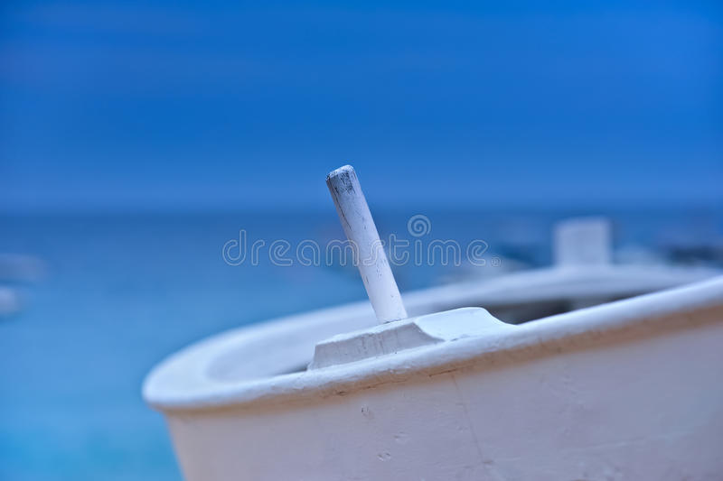 Close-up of oar pin. Close-up of the oar pin of an old, white-painted wooden fishing boat. Set against the out of focus horizon between a vibrant blue sea and stock photo