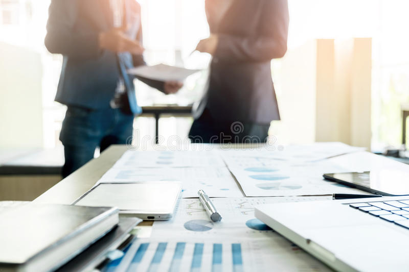 Close-up of office desk with business team discussting work project behind royalty free stock image