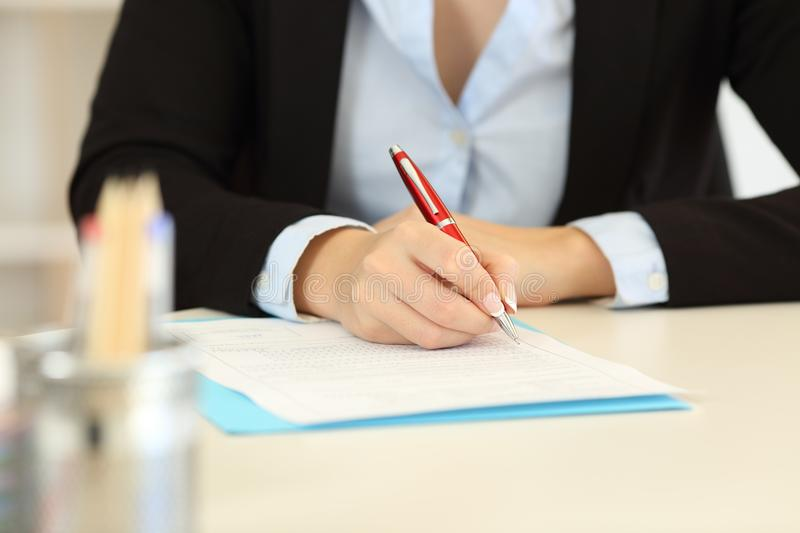 Close up of an office worker hands filling form royalty free stock images