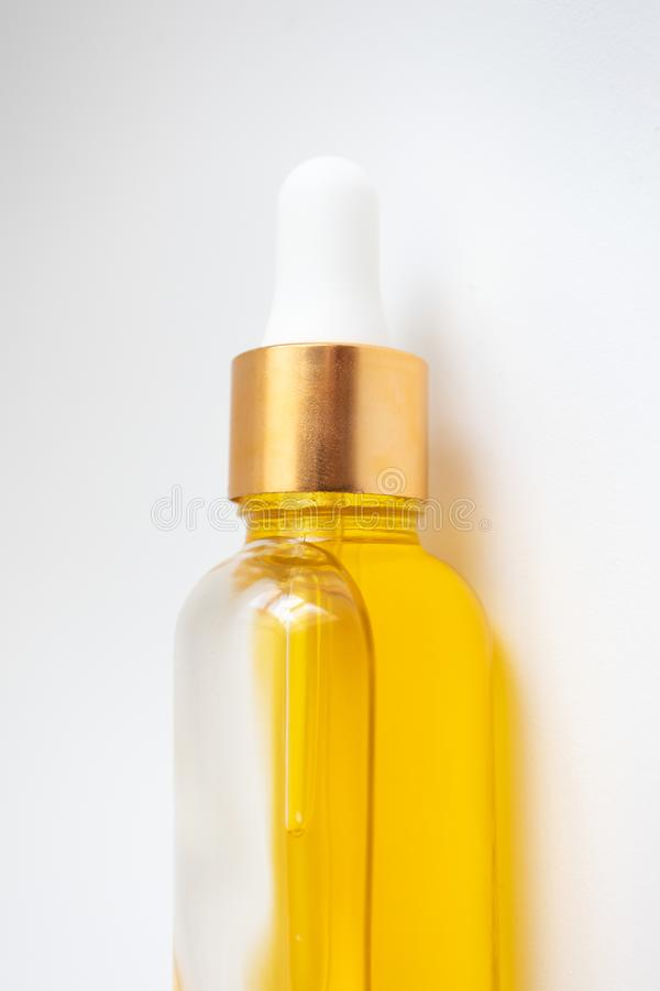 Close-up oil serum essence in glass bottle. Macro skincare product vertical photo. Close-up oil serum essence in glass bottle on white background. Macro skincare stock photos