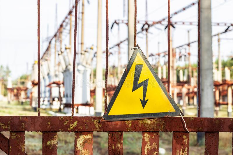 Close-up old aged rusty triangle metal plate with High voltage warning sign. Power station with transformers and electricity. Distribution lines. Keep out stock photo