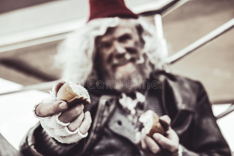 Close up of old almsman whose holding pieces of baking and sharing it with photographer. royalty free stock photo