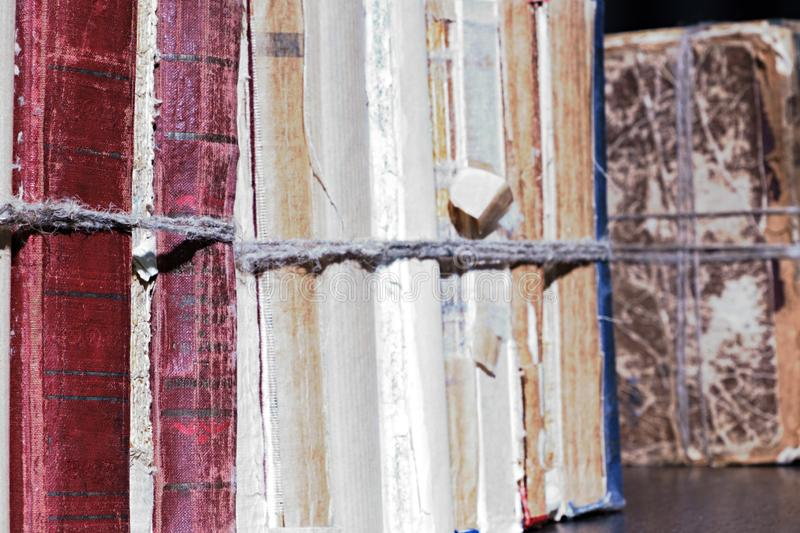 Close-up old books tied with a rope on wooden shelf in the Library or in the archive royalty free stock photos