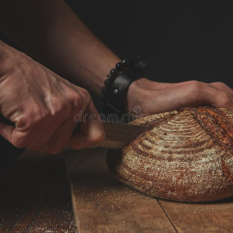 Man cuts a round dark bread royalty free stock photography