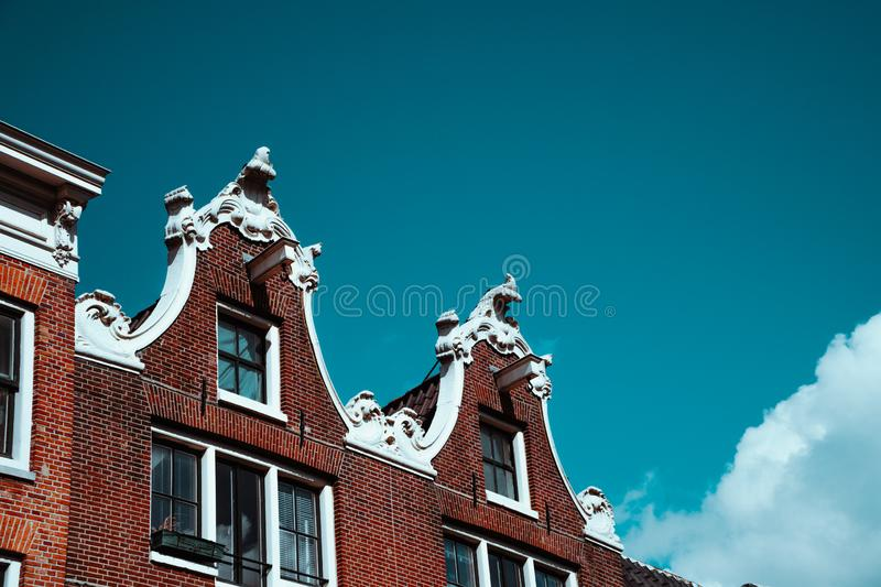 Close-up of old building facade and roof decoration against blue sky in Amsterdam. Architectonic Details Northern Netherlands royalty free stock images