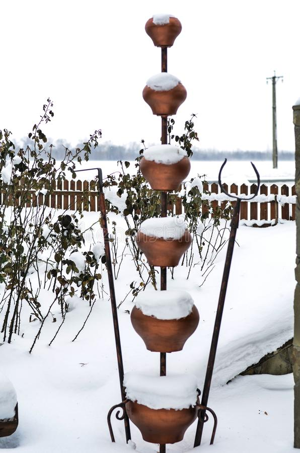 Close-up of old clay dippers of various sizes with a beautiful winter landscape in the background. stock photography