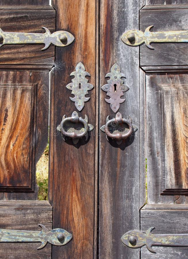 Close up of old cracked and broken wooden exterior double doors with ornate iron and brass handles keyholes and hinges royalty free stock photo