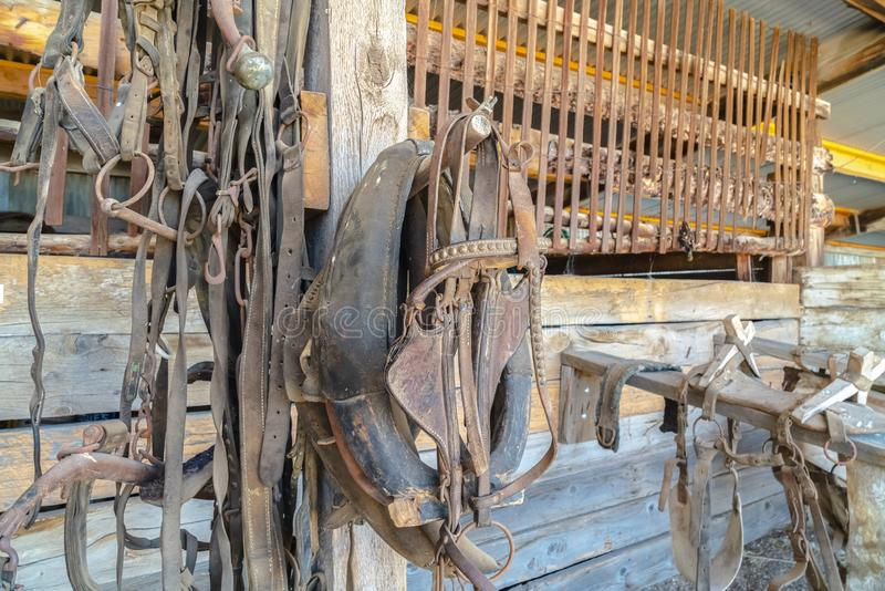 Close up of old and dirty horse saddle with rusty metal and damaged leather. Deteriorated and abandoned horse riding equipment inside a rustic barn stock images