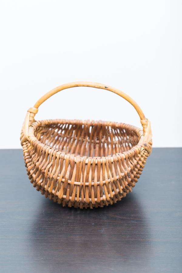 Close up of old empty willow basket. Standing on dark wooden table. Traditional container royalty free stock images