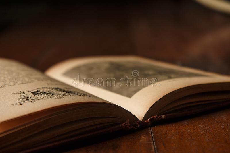 Old book of fables opened on old rustic wooden table, number one in evidence on the back. Background with soft blur and sullen app stock image
