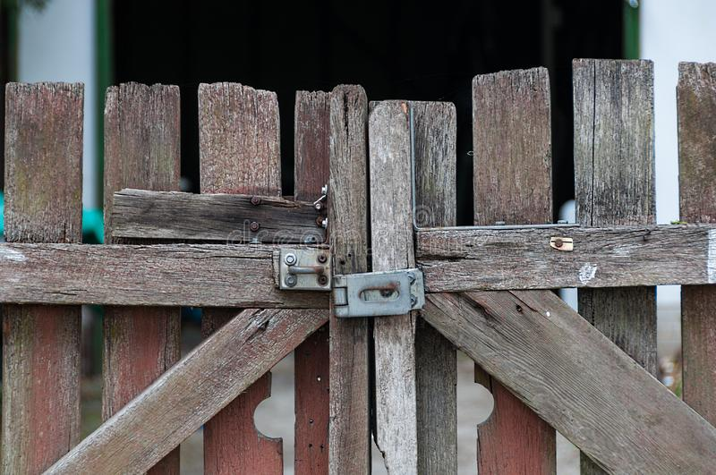 Close up of old farm gate with the metal door latch. Closed weathered plank paddock door stock image