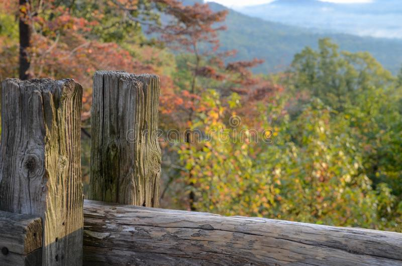 Close up of an old fence post with blurred fall color trees in the distance. stock image
