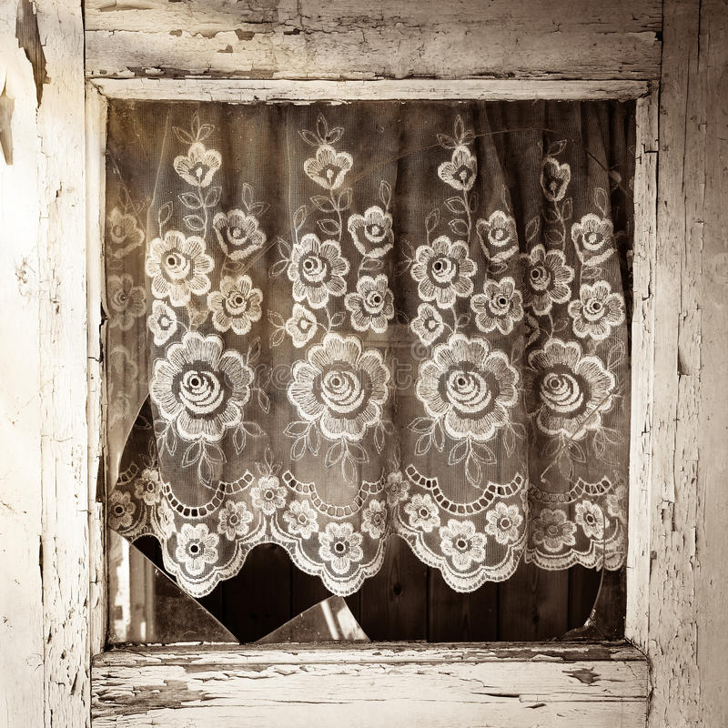 Close up of old house door window frame with broken glass. And with white flower pattern curtain stock image