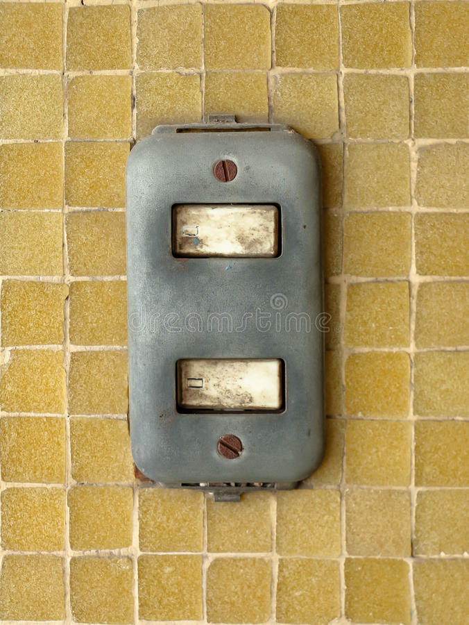 Close-up of old light switch on yellow mosaic wall as modern technology concept, in contrast. The old light switch block with a rust knot on yellow mosaic wall royalty free stock photos