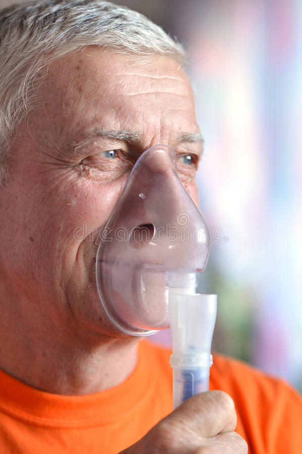 Old man doing inhalation stock image