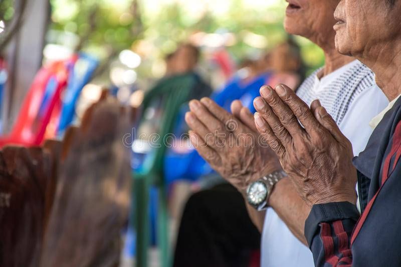Close-up of an old man raising his hand to pay respect to the Buddha in a Thai temple stock image