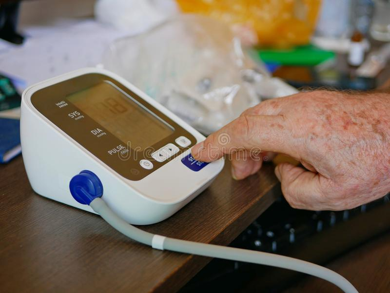 Selective focus of an old man`s hand placed next to the monitor checking his blood pressure at home by himself royalty free stock image