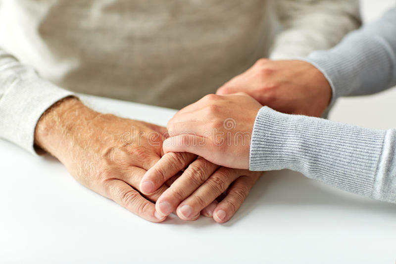 Close up of old man and young woman holding hands royalty free stock photos