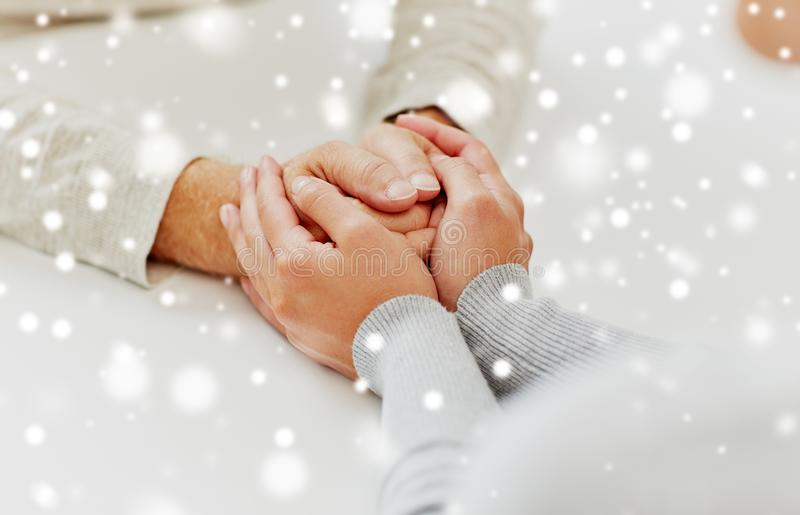 Close up of old man and young woman holding hands royalty free stock images