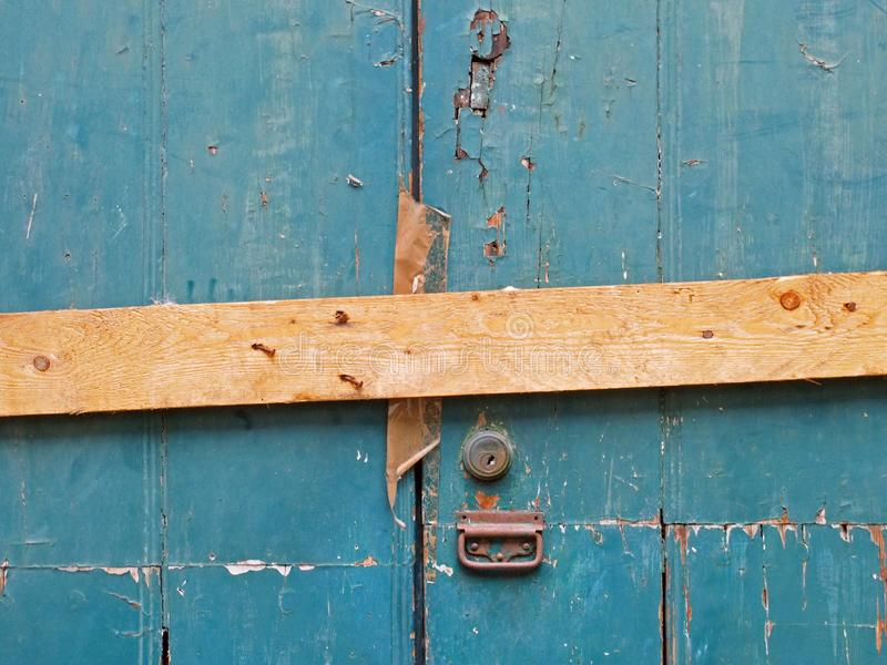 Close up of an old peeling green painted wooden plank door barred shut with a piece of timber and rusty nails with a lock and. Handle royalty free stock photo