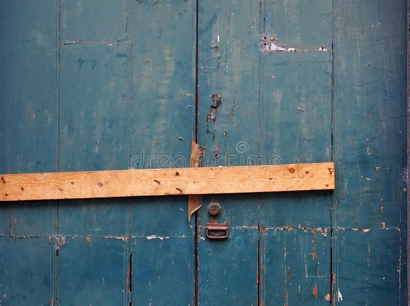 Close up of an old peeling green painted wooden plank door barred shut with a piece of timber and rusty nails with a lock and. Handle royalty free stock image