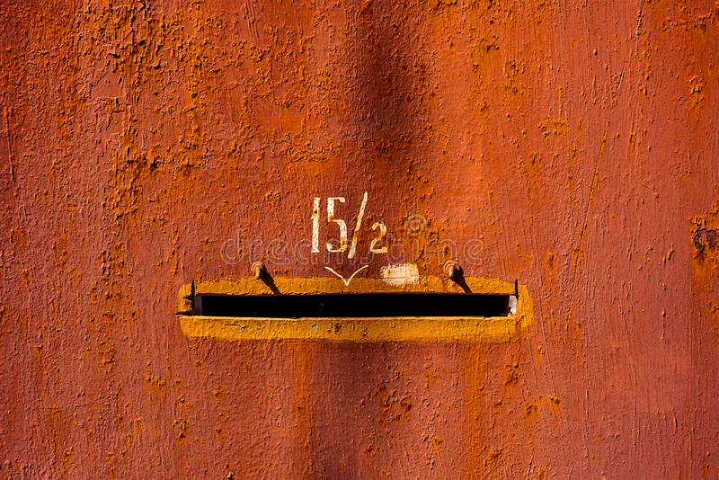 Close-up old red painted metal door with number fifteen fractions two and mail hole. Horizontal texture of cracked paint royalty free stock images