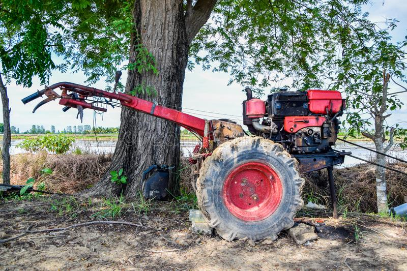 Close up of the old red tiller tractor or walking tractor parked under the tree in the fields at countryside, Thailand. Old tractor for walking plow is parking stock images