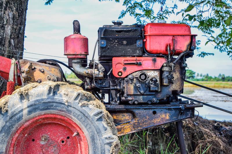 Close up of the old red tiller tractor or walking tractor parked under the tree in the fields at countryside, Thailand. Old tractor for walking plow is parking stock image