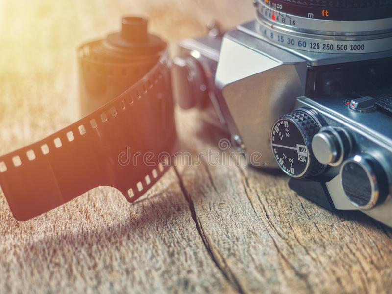 Close-up on old retro 35mm film SLR camera with photographic film resting on a wooden table royalty free stock photo