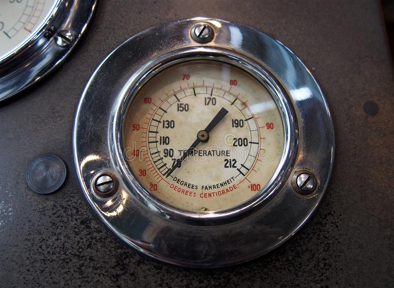 Close up of an old round metal temperature gauge with the meter reading in Fahrenheit and Celsius with a shiny chrome surround. Mounted on the control panel of royalty free stock photo