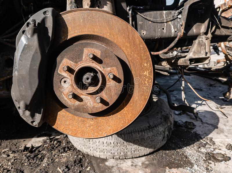A close-up on the old rusty brake system of a car with pads, discs, a caliper on a lift in a vehicle repair workshop. Auto service royalty free stock photo