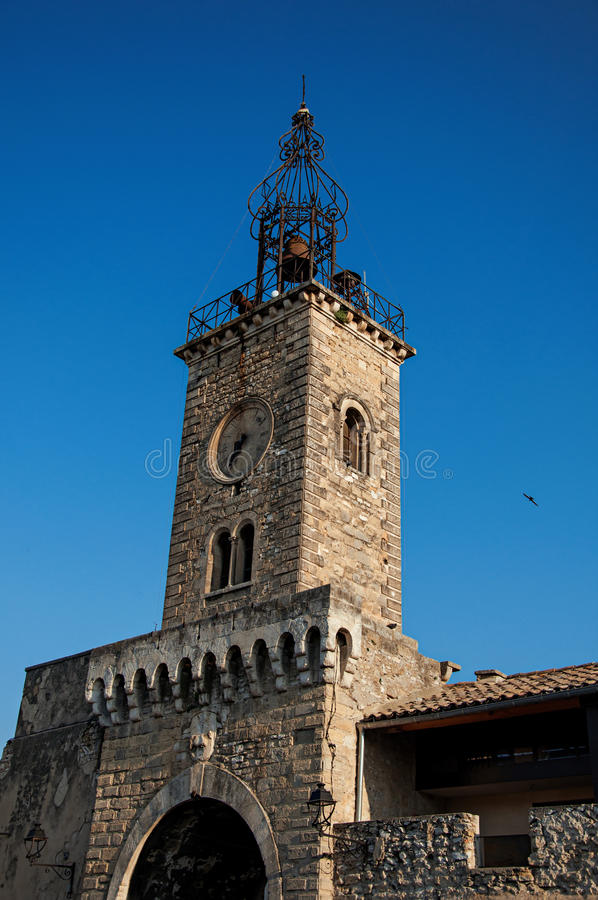 Close-up of old stone tower at sunrise, with clock and bell, in Le Thor. royalty free stock photography