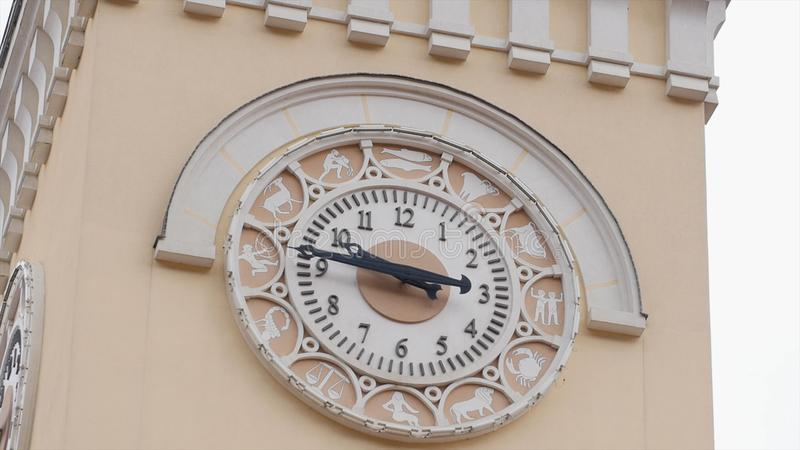 Close-up of old tower clock. Clock tower with old simple style of dial is surrounded by signs of zodiac. Architecture of. Old clock tower royalty free stock images