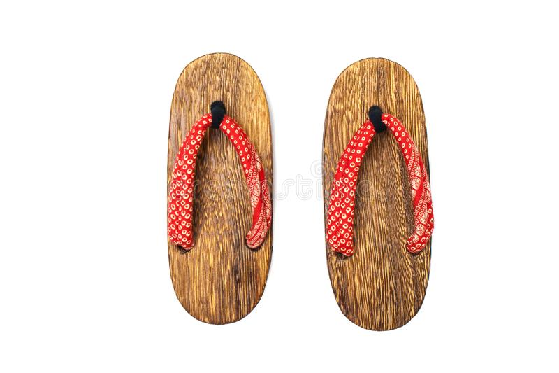 Close up old used wooden Japanese sandal isolated on white background. stock photography