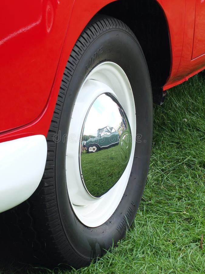 Close up of an old vw combi van wheel with a vintage green mini reflected in the chrome hubcap at the Hebden Bridge Vintage Weeken. Hebden Bridge, West Yorkshire stock image