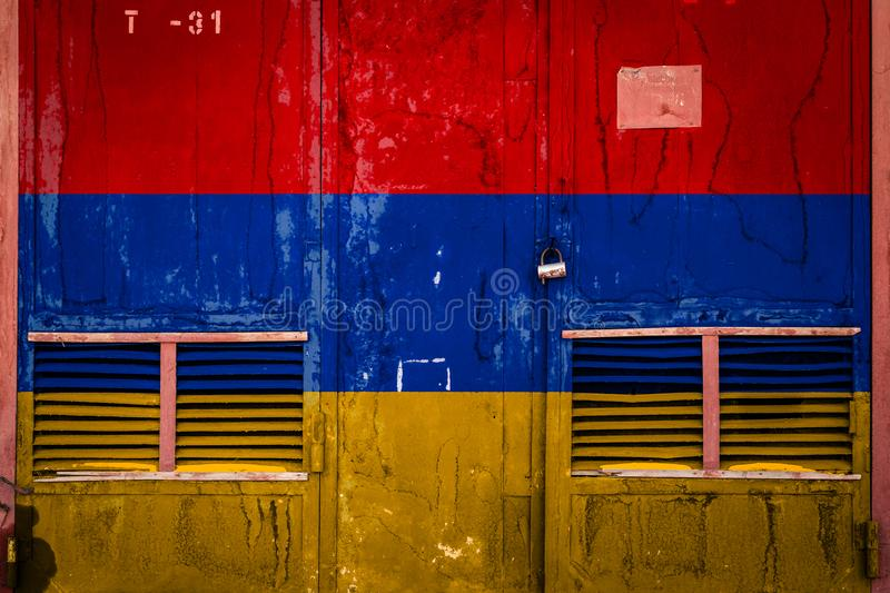 Close-up of old warehouse gate with national flag. Of Armenia. Concept of Armenia export-import, storage of goods and national delivery of goods. Flag in grunge royalty free illustration