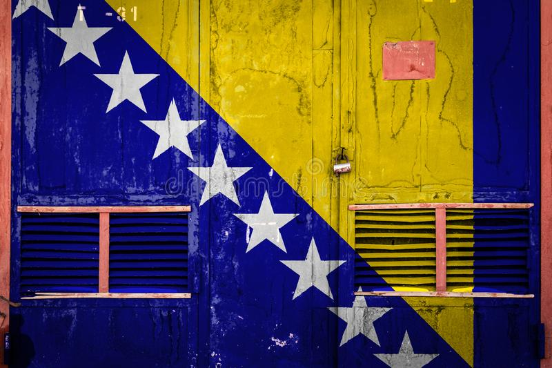 Close-up of old warehouse gate with national flag. Of Bosnia Herzegovina. Concept of  Bosnia Herzegovina export-import, storage of goods and national delivery stock illustration