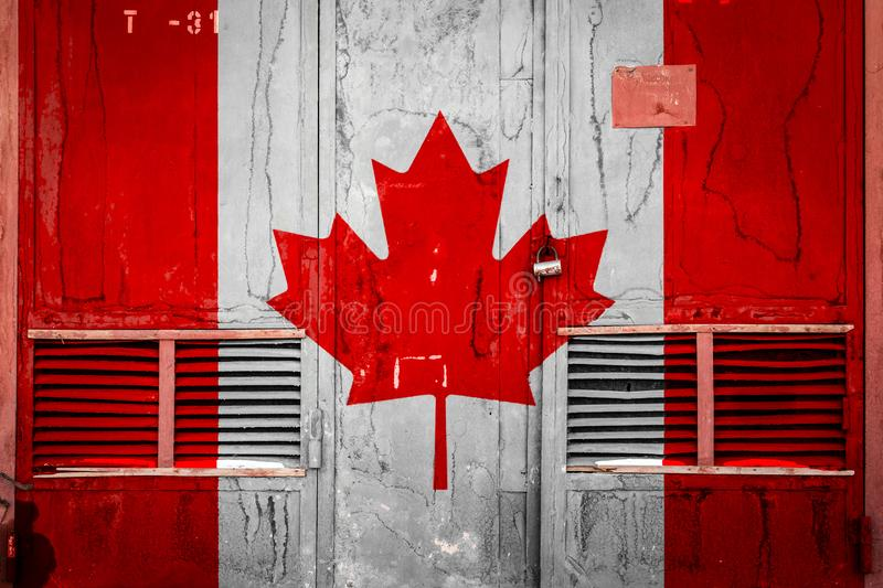 Close-up of old warehouse gate with national flag. Of Canada. Concept of Canada export-import, storage of goods and national delivery of goods. Flag in grunge stock illustration